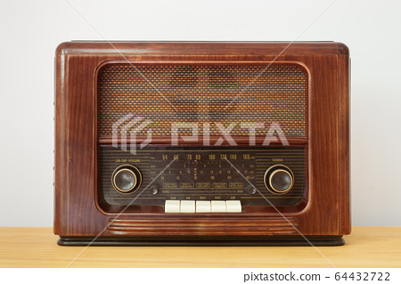 Front color view image of a vintage radio made of wood on a table 64432722