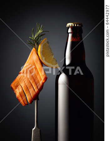 Bottle of beer and smoked squid . 64442977