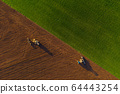 Harvesters working in the field at spring and plowing the field. Sowing work 64443254