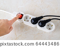 Woman hand going to push power button on a white extension cord with four outlets. 64443486