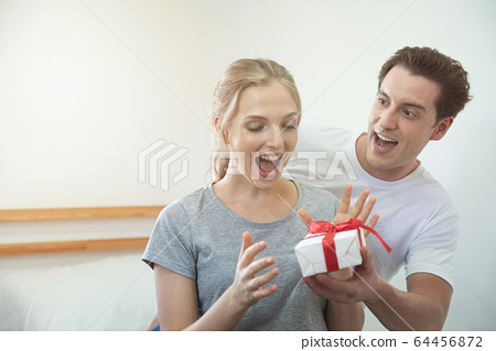 Happy young caucasian couple celebrating at home. 64456872