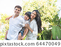caucasian asian family man piggyback little boy and mom hug from back standing outdoor yard  64470049