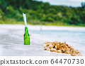 Bottle with message on white paradise sandy beach with blurred jungle in background conceptual 64470730