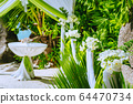 Decorated romantic wedding celebration location, table and chairs on tropical beach. Lush green foliage and white lowers 64470734