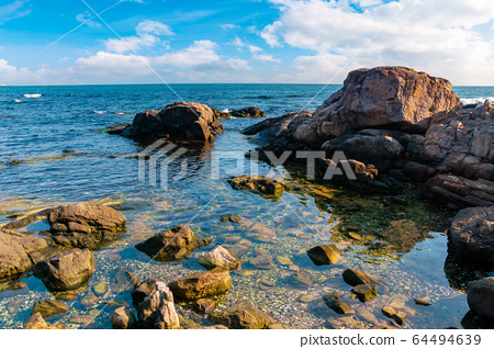 rocky shoreline of the sea in the morning. 64494639