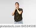 Portrait of shocked, speechless asian guy gasping, cover mouth and express shook and surprised with eyes, gazing camera at unbeliavable amazing thing, standing grey background 64504508