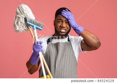 Worry African Man With Mop And Broom, Touching Head In Despair 64524129