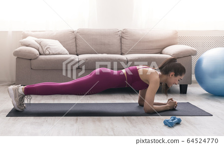 Self isolation activities. Sportswoman making plank exercise at home. Panorama 64524770