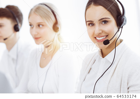 Call center in sunny office. Group of diverse operators at work. Beautiful woman in headset communicating with customers of telemarketing service. Business concept 64533174