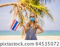 Happy woman in medical mask having fun at the beach with Thailand flag. Beautiful girl enjoying 64535072