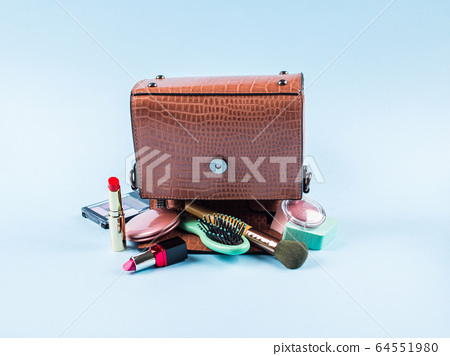 Lady hand bag upside down with make up items 64551980