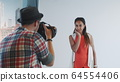 Backside view of photographer taking photo of beautiful multiracial model in studio 64554406