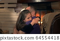 Happy father and small daughter embracing each other on armchair near the fireplace 64554418