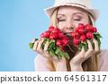 woman holding radish close to face 64561317