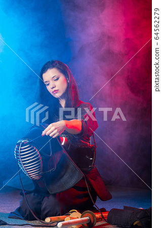 young woman kendo fighter wear mask helmet on head 64562279