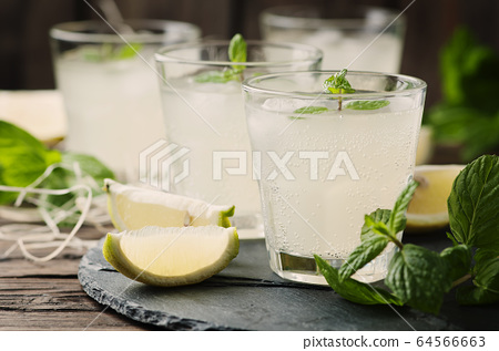 Fresh cocktail with lemon, ice and mint on the 64566663