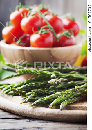 Raw asparagus with tomato on the wooden table 64567737