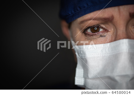 Tearful Stressed Female Doctor or Nurse Crying Wearing a Face Mask 64580014