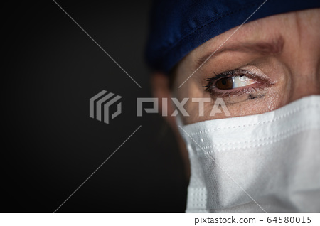 Tearful Stressed Female Doctor or Nurse Crying Wearing a Face Mask 64580015