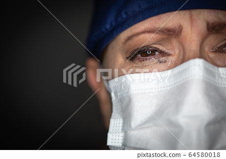 Tearful Stressed Female Doctor or Nurse Crying Wearing a Face Mask 64580018