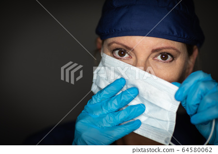 Female Doctor or Nurse Wearing Surgical Gloves with A Face Mask 64580062
