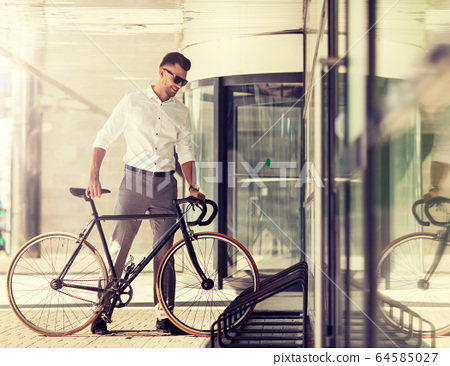 young man parking his bicycle on city street 64585027