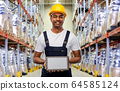 happy indian worker with tablet pc at warehouse 64585124