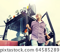 old man or farmer getting out of tractor at farm 64585289