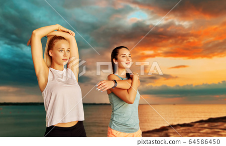 women with fitness trackers stretching over sea 64586450