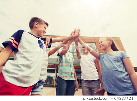 group of children making high five at school yard 64587421