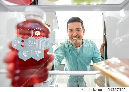 man taking juice from fridge at home kitchen 64587502