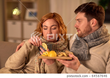 sick young couple drinking tea with lemon at home 64587646