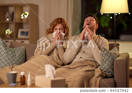 sick young couple with tissue blowing nose at home 64587942