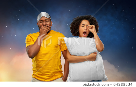african couple with eye sleeping mask and pillow 64588334