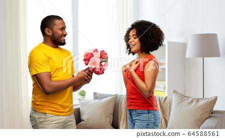 happy african american couple with flowers 64588561