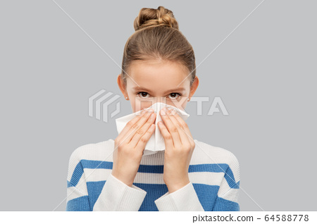 sick teenage girl blowing nose with paper tissue 64588778