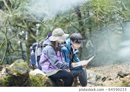 Couple looking at a map while climbing 64590233