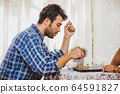 Latin man playing chess board game at home for holiday activity with his family he thinking 64591827