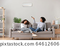 Happy african american family relaxing on sofa under air conditioner 64612606