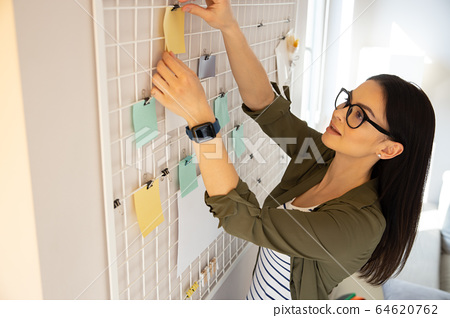 Calm lady sticking memo note on her mesh board on the wall 64620762