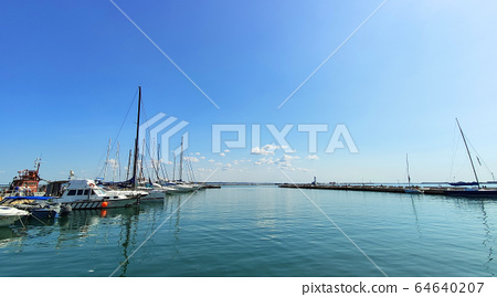 Wooden pier with many yachts stand and prepare for regatta, calm sea and small clouds in the sky 64640207