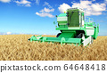 modern combine harvester working on a wheat crop 64648418
