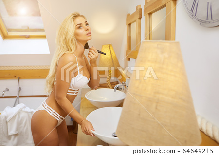 Blonde beautiful woman doing makeup in front of 64649215