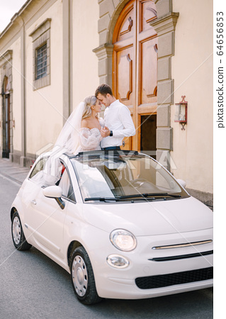 Beautiful bride and groom standing up and leaning forehead to forehead in a convertible in front of Medici Villa of Lilliano Wine Estate, Tuscany, Italy. 64656853