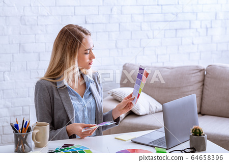 Woman with color swatch and laptop working during epidemic 64658396