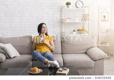 Stay home, drink coffee. Millennial girl with cup of hot beverage relaxing on comfy sofa in living room, copy space 64658489