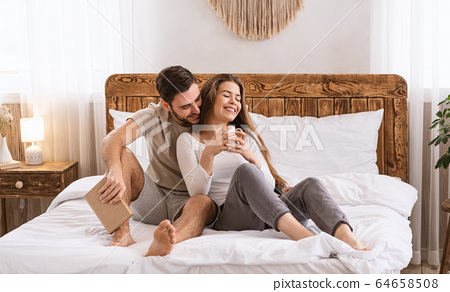 Guy with book, girl with cup on bed 64658508
