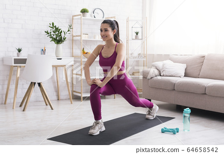 Stay home, stay active. Latin girl doing cardio workout in living room 64658542