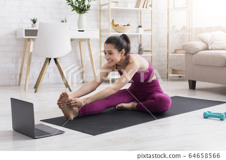 Self isolation workout. Joyful girl in sportswear practicing yoga or stretching with online tutorial at home 64658566
