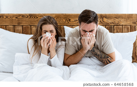 Couple in bed wiping nose with napkins 64658568